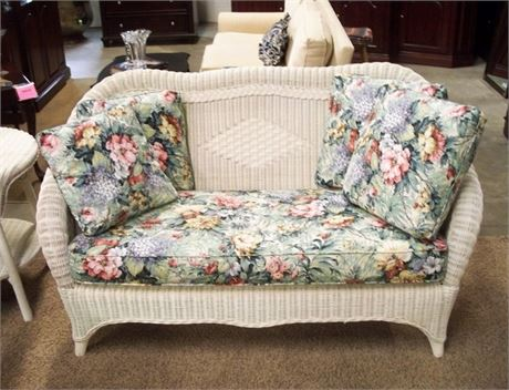 WHITE WICKER LOVESEAT WITH FLORAL SEAT CUSHION AND 4 THROW PILLOWS