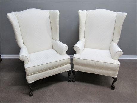2 CREAM COLORED HIGH-BACK WING-BACK FIRESIDE CHAIRS WITH BALL AND CLAW FEET