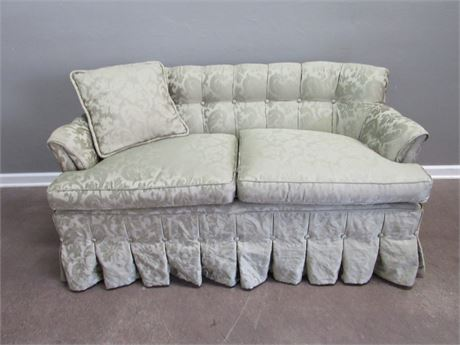 Green Upholstered Loveseat with Throw Pillow
