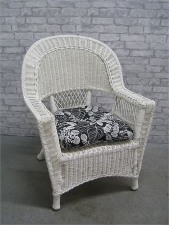 WHITE WICKER CHAIR WITH BLACK AND WHITE FLORAL CUSHION